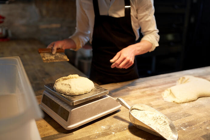 chef-or-baker-weighing-dough-on-scale-at-bakery-PUM8VLM