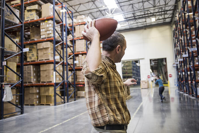 warehouse-employees-playing-catch-with-an-american-4CFPBN2
